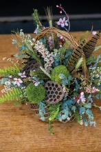 May basket with flowers and feathers