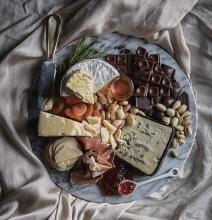 A spread of cheese, chocolate, fruit and nuts.