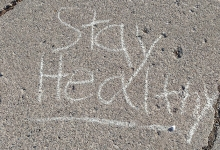 """Stay Healthy"" written in chalk on a sidewalk."