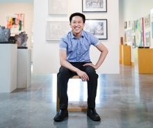 Vincent Cao, a member of the 2019 Senior Spotlight, sits in front of a wall of art.