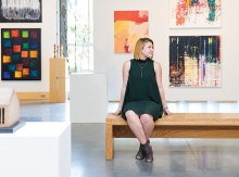 Grace Hanson, part of the 2019 Senior Spotlight, poses in front of a wall of paintings.
