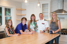 A military family poses for a photo in their kitchen.