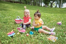 Two babies wearing RubyScootz play on a lawn.