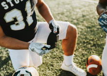 A football player holds a NoSweat liner for their helnet.