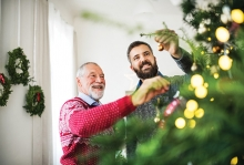 Two men decorate a Christmas tree