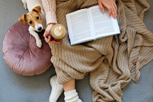 Woman reading while snuggled with dog
