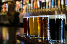 A flight of craft beers sits on a bar. Behind, a row of craft beers on tap.