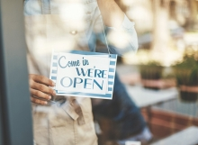 """A shop celebrating Small Business Saturday hangs a """"Come in we're open"""" sign in the window."""
