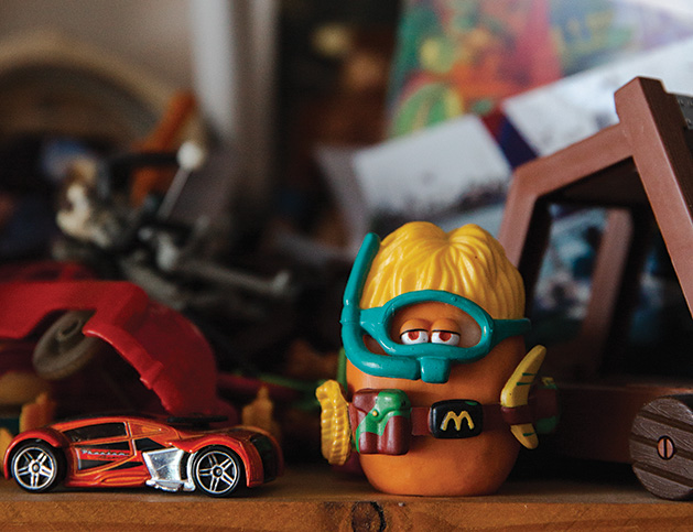 A toy car and toy McDonald's chicken nugget on C. Ray Frigard's shelf