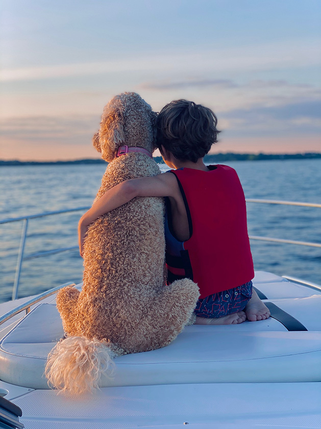 A boy sits with his dog on a boat on Lake Minnetonka