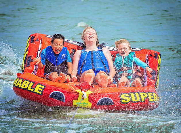 Three children laugh while tubing on Lake Minnetonka.